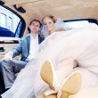 Newlyweds drinking champagne in their limo — Stock Photo
