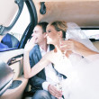 Newlyweds drinking champagne in their limo - Stock Photo