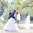 Wedding shot of bride and groom embracing in park — Stock Photo