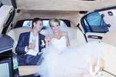 Newlyweds drinking champagne in their limo — Stockfoto
