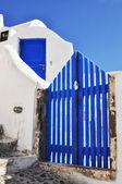 Modré dřevěné dveře a jasné modré nebe na santorini island, řecko — Stock fotografie