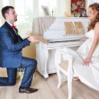 Happy married couple near the piano — Stock Photo #27193613