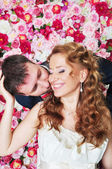 Newly married couple in rose petals — Stock Photo