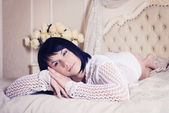 Beautiful dark haired girl in bed — Stock Photo