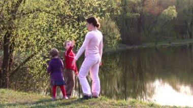 Mother with children on spring pond — Stock Video