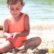 Little girl play with sand on beach — Stock Video #12309946