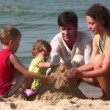 Family of four play with sand — Stock Video