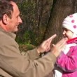Senior with little girl in autumn park play by hands — Stock Video