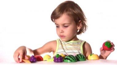 Kleines mädchen mit kunststoff früchte — Stockvideo