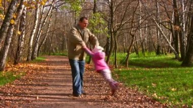 Grandfather rotate child in autumn park — Stock Video