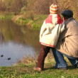 Senior with child. Ducks on pond - Stock Photo