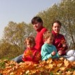 Family of four sit in autumn leaves — Stock Video
