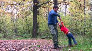 Father rotating girl in autumn wood — Stock Video