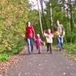 Family of four running in autumn park. — Stock Video
