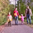 Stock Video: Family of four walking in autumn park.