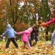 Family of four person throw autumn leaves. — Stock Video