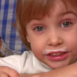 Vídeo Stock: Smiling little girl with kefir moustaches.