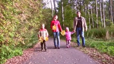 Family of four walking in autumn park. — Stock Video
