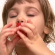 Stock Video: Little girl eats tomato