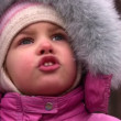 Little girl talking in winter park, closeup - Stock Photo