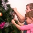 Children hangs up fur-tree toy on christmas tree — Stock Video