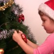 Little girl hangs up fur-tree toy on christmas tree — Stockvideo