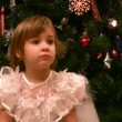 Little girl sits on chair near christmas tree — Stock Video