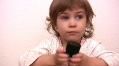 Little girl pushing buttons and talking by phone — Stock Video