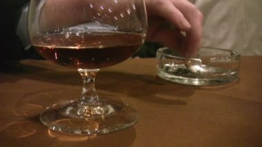 Person shakes ashes from cigarette and cognac glass — Stock Video