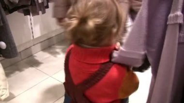 Little girl watching clothes in shop — Stock Video #12358138