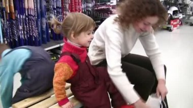 Mother with children trying skates in shop — Vídeo de Stock