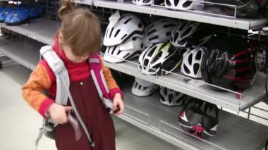 Little girl with knapsack in shop, bicycle helmets — Stock Video