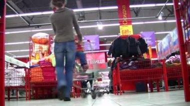 Mutter dreht kind im warenkorb im shop — Stockvideo