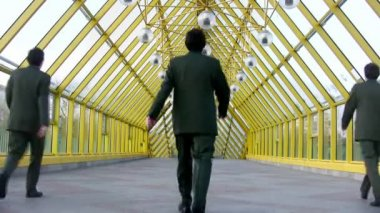 Behind marching businessmen clones on bridge — Stock Video #12359860
