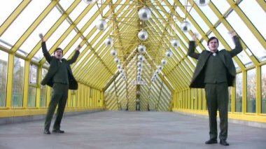 Jumping happy two businessmen on bridge — Stock Video