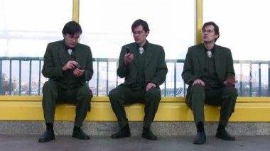 Three businessmen clones sit near window — Stock Video