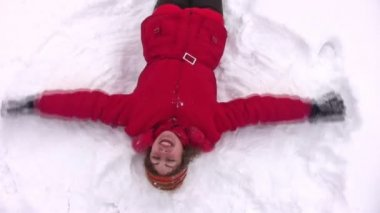Woman lies on snow with hands as wings