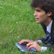 Handsome man profile typing on keyboard lying on green grass — Stock Video