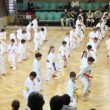 Kids in sports hall are doing exercise on promotion examination in style of Goju-ryu Karate-Do — Stock Video
