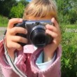 Portrait of little girl with photo camera in park - Stockfoto