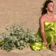 Stock Video: Beautiful womwho has been wrapped up in fabric sits on sand