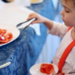 Small girl places piece of the tomato in plate - Stock Photo