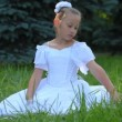 Girl in white dress sits on grass and touches it with her hand - Stockfoto