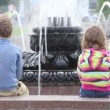 Boy and girl seating at fountain — Stock Video #13786767