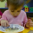 Little girl eating porridge in the kindergarten - Stock Photo