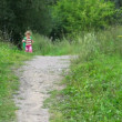 Little girl with rucksack running in park to camera — Stock Video