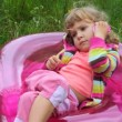 Little girl sitting on inflatable armchair andspeaking on the phone - Foto Stock