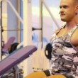 Bodybuilder exercising with dumbbells in gym — Stock Video