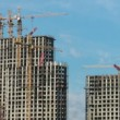 Under construction houses and cranes against the sky - Stock Photo