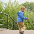 Kids with dog running on bridge, from camera — Stock Video